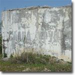 Полустершиеся буквы СЛАВА ТРУДУ на стене какого-то здания. Фото ИА Фергана.Ру