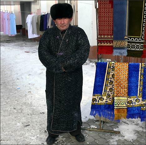 Торговец на рынке Ташкента в национальном узбекском халате - чапане