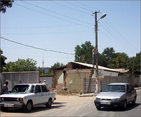 Дом №84 по улице Кичик Бешёгоч, половина которого уже снесена. Монтер отрезает телефонную линию