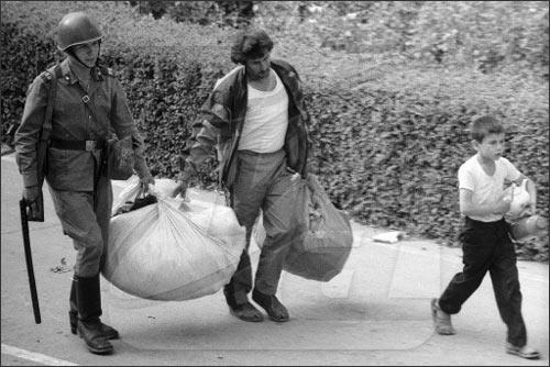 Солдаты внутренних войск помогают беженцам нести нехитрый скарб
