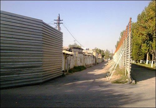 Махалля, идущая на слом, закрыта от посторонних глаз длинным забором
