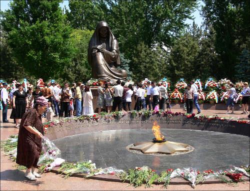 Граждане возлагают цветы к подножию монумента Скорбящей матери на площади Памяти