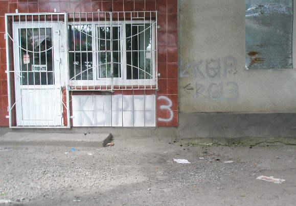 Ош. Район Фрунзенского рынка. Удивительно, но между сгоревших зданий абсолютно нетронутыми (даже с непобитыми стеклами) остались маленькие магазинчики, аптеки, и прочее  - все, где  написано «кыргыз».