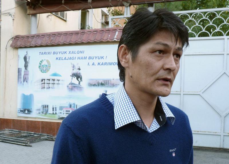 Абдумалик Бобоев на фоне плаката с цитатой из Ислама Каримова про государство с великим будущим