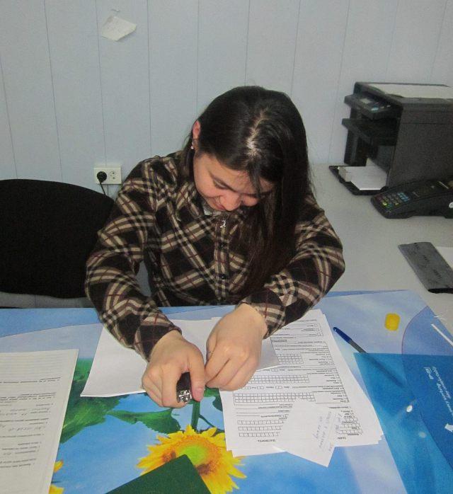 Девушка-сотрудница стола услуг оформляет ваши документы
